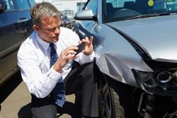Stock photo of an insurance adjuster inspecting damage to a car that's been in an accident