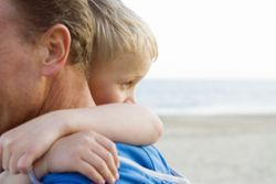 Stock photo of a young boy hugging his father on the ocean.