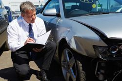 Stock photo of an insurance agent examining damage to a vehicle following an accident.