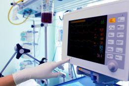 Stock photo of a nurse examining medical equipment inside a hospital room.