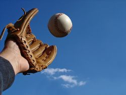 Stock photo of a man catching a baseball with a baseball glove