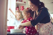 Stock photo of a mother cooking in the kitchen with her small children.