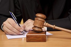 Stock photo of a judge signing a legal document.