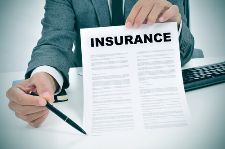 Stock photo of an insurance agent prompting an individual to sign insurance documents.