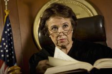 Stock photo of an elderly female judge sitting on the bench inside a courtroom.