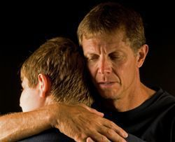 Stock photo of a father hugging his teenage son in mourning.