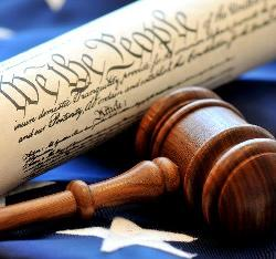Stock photo of a judge's gavel laying on top of an American flag